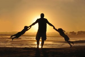 father holding children's hands in sunset