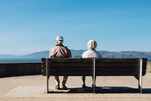 elderly couple sitting on bench with view in retirement
